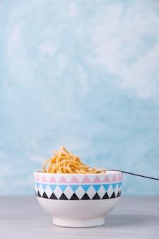 Nouilles à la sauce dans un bol coloré avec fourchette, spaghetti appétit sur bleu.