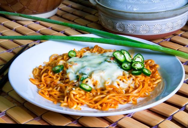 Nouilles sauce épicée à la coréenne sur du fromage fondu décoré d'une tranche de piment vert et d'oignons verts posés sur une plaque blanche