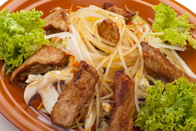 Nouilles sautées au boeuf et aux légumes. garni de feuille de salade