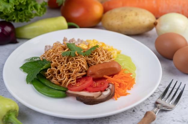 Nouilles sautées au porc haché, edamame, tomates et champignons dans une assiette blanche.