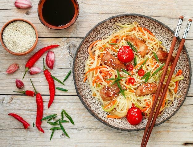 Nouilles sautées au poulet, légumes, graines de sésame et sauce soja sur plaque d'argile