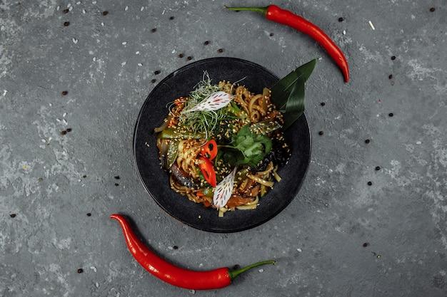 Nouilles sautées et légumes dans un bol noir