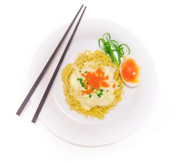 Nouilles sautées à la sauce au jaune d'œuf sur du fromage fondu et parsemées d'oignons de printemps et d'ebiko