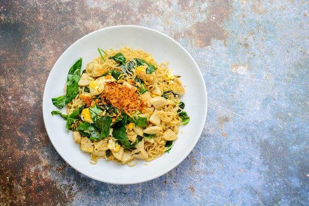 Nouilles sautées à la saucisse de porc grillée vietnamienne, œufs et feuilles de gneton gnetum