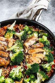 Nouilles sautées udon au poulet dans une poêle. vue de dessus.