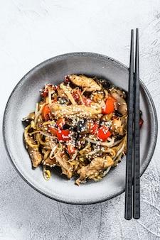 Nouilles sautées udon avec viande de poulet et sésame sur fond gris. vue de dessus