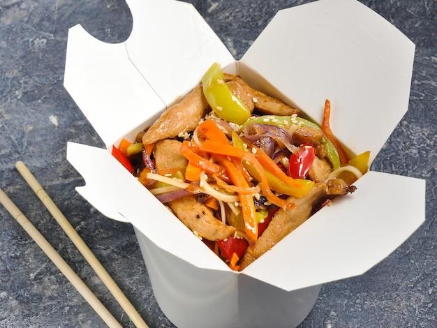 Nouilles savoureuses au wok au poulet et légumes dans une boîte sur un fond gris