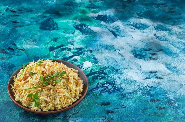 Nouilles savoureuses faites maison dans un bol, sur la table bleue.