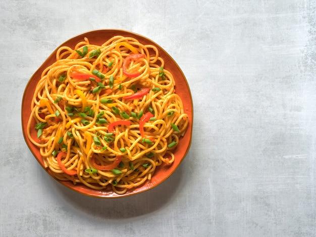 Nouilles schezwan aux légumes dans une assiette. vue de dessus.