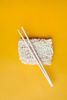 Nouilles sèches avec des baguettes sur fond jaune espace de copie