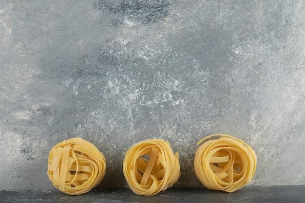 Nouilles sèches crues de nid sur une table de marbre.