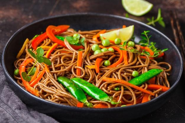 Nouilles soba végétaliennes au sarrasin avec légumes dans une assiette noire.