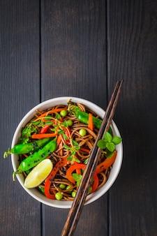 Nouilles soba végétaliennes au sarrasin avec légumes, vue de dessus.