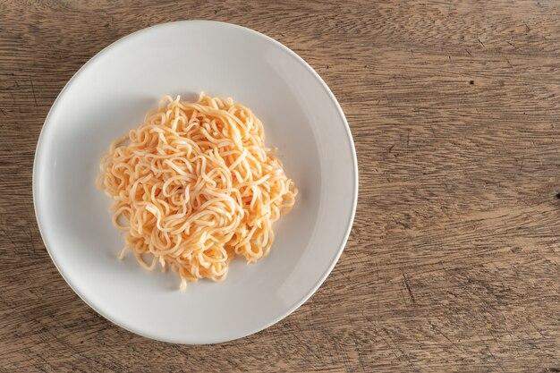 Les nouilles sont dans une assiette blanche ronde placée sur une table en bois.