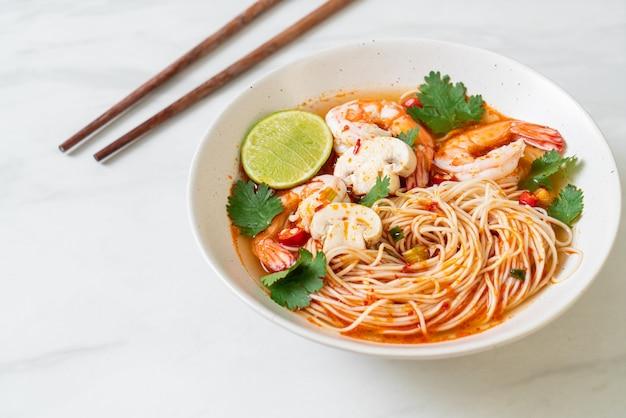 Nouilles avec soupe épicée et crevettes dans un bol blanc (tom yum kung) - style de cuisine asiatique