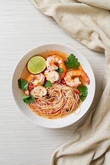 Nouilles avec soupe épicée et crevettes dans un bol blanc (tom yum kung)