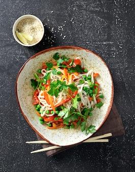 Nouilles thaïlandaises aux légumes sur fond sombre vue de dessus