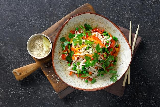 Nouilles thaïlandaises aux légumes sur la vue de dessus de table sombre