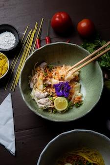 Nouilles thaïlandaises et ingrédients aromatisants placés sur une table en bois