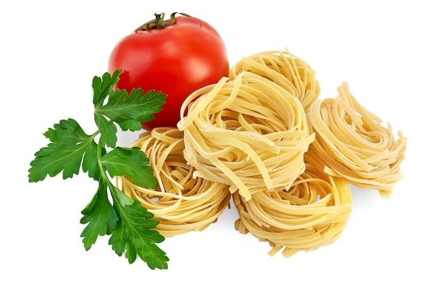 Nouilles torsadées brutes avec tomate rouge et persil vert isolés sur fond blanc