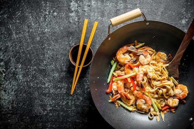 Nouilles udon asiatiques fraîchement cuites dans un wok avec sauce soja et baguettes. sur table rustique sombre