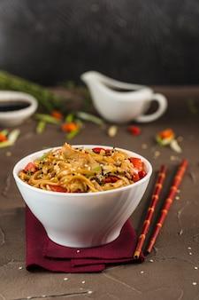 Nouilles udon au poulet et légumes dans une assiette avec des baguettes rouges et de la sauce soja.