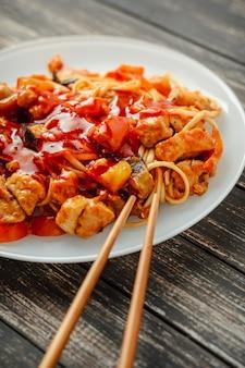 Nouilles udon au poulet et légumes dans une assiette blanche se bouchent
