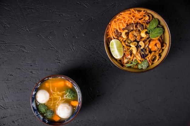 Nouilles udon frites avec boule de poisson et soupe de légumes sur fond texturé en béton noir