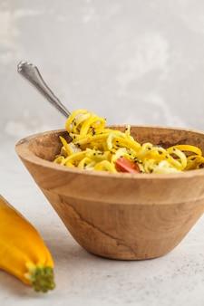Nouilles végétaliennes brutes de courgettes au tofu et aux tomates dans un bol en bois.