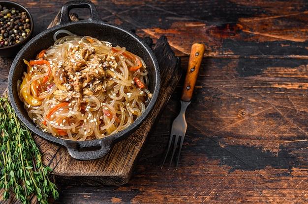 Nouilles en verre de soja aux champignons shiitake et viande de poulet. fond en bois. vue de dessus. copiez l'espace.