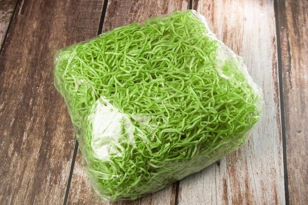 Nouilles vertes aux légumes en pack sur fond de bois