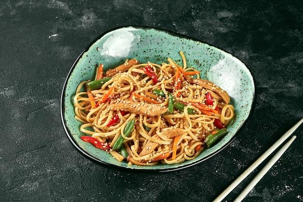 Nouilles wok udon au sarrasin avec poulet, sauce coriandre aux légumes dans une assiette verte. gros plan, mise au point sélective