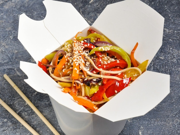 Nouilles wok végétariennes savoureuses dans une boîte sur un fond gris
