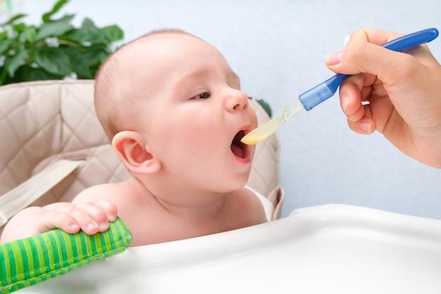 Nourrir le bébé. maman nourrit l'enfant de purée de légumes avec une cuillère. heureux enfant assis sur une chaise haute attachée