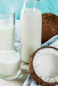 Nourriture alternative végétalienne, lait de coco non laitier sur fond bleu clair, espace copie