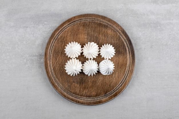 Nourriture bizet sucrée blanche et rose placée sur une assiette en bois.