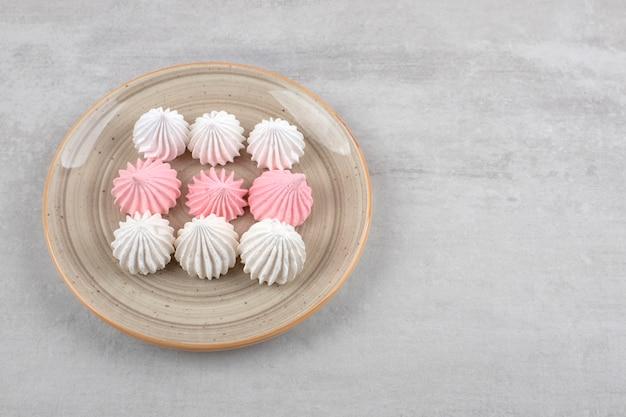 Nourriture bizet sucrée blanche et rose placée sur une assiette.