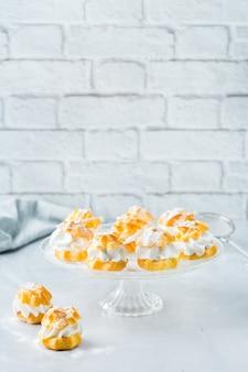 Nourriture et boisson, concept de vacances. délicieuses profiteroles maison sucrées à la crème sur une table de cuisine moderne. copier l'arrière-plan de l'espace
