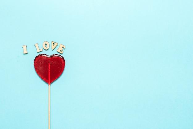 Nourriture et boisson, concept de vacances. sucette en forme de coeur pour l'amour saint valentin avec mur turquoise. copier l'espace