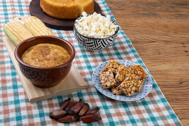 Nourriture brésilienne typique de festival de juin sur la nappe sur le fond en bois