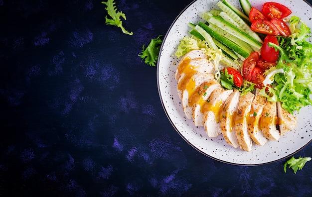 Nourriture cétogène, céto. filet de poulet frit et salade de légumes frais de tomates, concombres et laitue. viande de poulet avec salade. la nourriture saine. vue de dessus, mise à plat, espace de copie