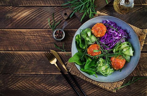 Nourriture cétogène / cétogène. boulettes de poulet et salade sur table en bois. dîner. bol de bouddha. vue de dessus, frais généraux.