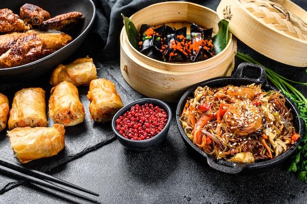 Nourriture chinoise. nouilles, boulettes, poulet sauté, dim sum, rouleaux de printemps. ensemble de cuisine chinoise. vue de dessus