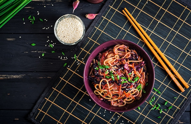 Nourriture chinoise. nouilles sautées végétaliennes au chou rouge et aux carottes dans un bol sur un fond en bois noir. repas de cuisine asiatique. vue de dessus