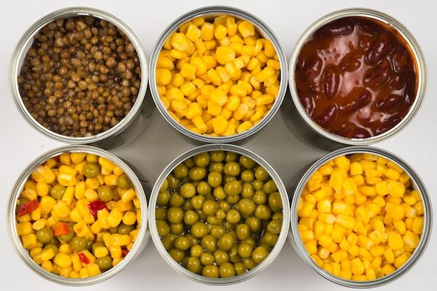 Nourriture en conserve sur fond blanc. pois verts, haricots, maïs, lentilles.