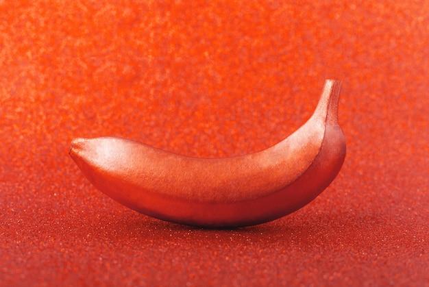 Nourriture couleur bronze, banane cuivrée sur rouge scintillant