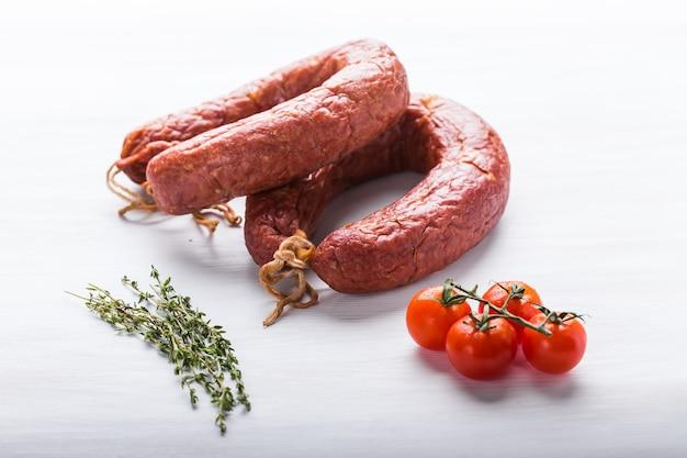Nourriture, cuisine nationale et concept délicieux - gros plan sur une saucisse de viande de cheval kazakhe traditionnelle avec tomate et cumin.