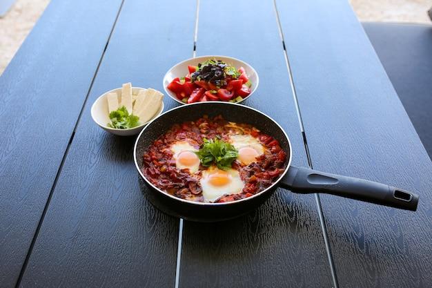 Nourriture dans la rue en été œufs au plat avec crevettes tamotami en été café avec œufs le petit déjeuner est servi sur la terrasse d'été shakshuka manger dehors en été petit déjeuner d'été à la maison