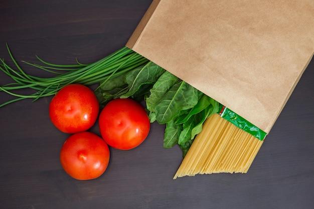 La nourriture dans un sac en papier sur une table en bois. tomates, oignons verts, macaroni.