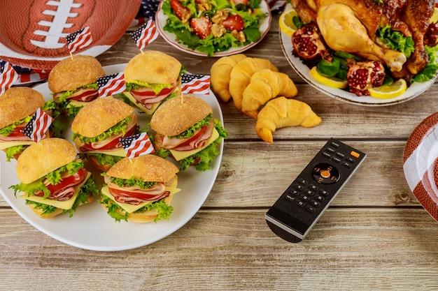 Nourriture délicieuse pour partie de match de football américain avec télécommande pour regarder le sport sur la chaîne de télévision.